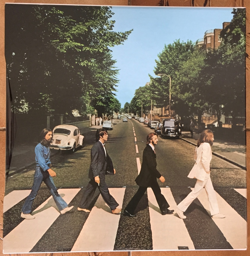 Front cover of the box set for Abbey Road by The Beatles, showing the 4 band members in a line striding across a zebra crossing.