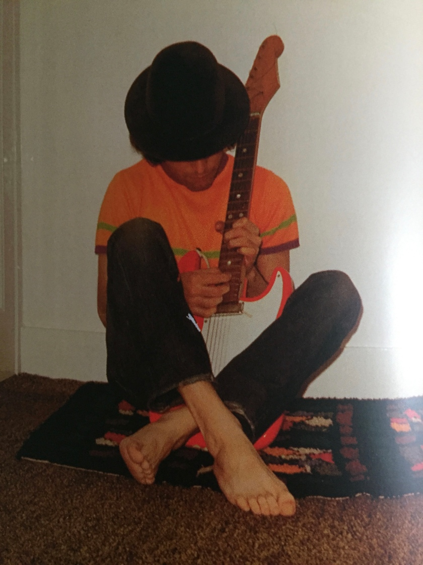 Photo of a young Freddie Mercury, wearing an orange t-shirt and black trousers and nothing on his feet, sitting cross-legged on the floor as he plays the guitar.