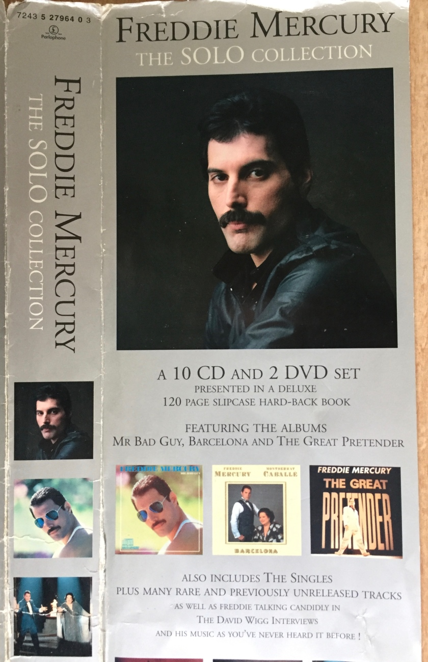 Section of the outer cover sheet of the Freddie Mercury Solo Collection box set. Photos show Freddie and the covers of his albums Mr. Bad Guy, Barcelona and The Great Pretender. Black text on the silver background says that it is a 10 CD and 2 DVD set, in a deluxe 120 page hardback book, featuring his albums, the singles, and many rare and previously unreleased tracks, plus the David Wigg interviews.