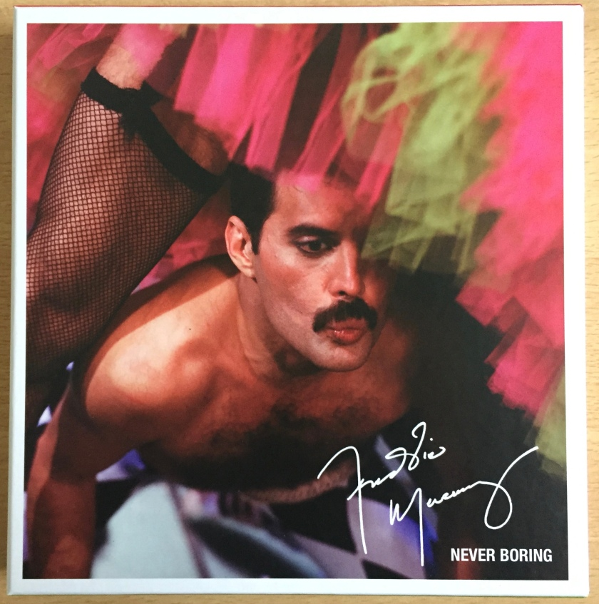 Cover of the Never Boring box set by Freddie Mercury. The image shows Freddie, topless and pouting his lips, as he dances between another person's legs, which are clad in fishnet stockings beneath a green and pink skirt. Freddie's signature is in white in the bottom right corner of the cover, above the title Never Boring.