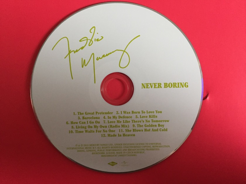 CD for the Never Boring compilation. The white disc contains green text, including Freddie Mercury's signature, the title Never Boring, and the list of tracks.