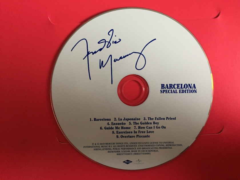 CD for Barcelona, Special Edition. The white disc contains dark blue text, including Freddie Mercury's signature, the title of the album, and the list of tracks.
