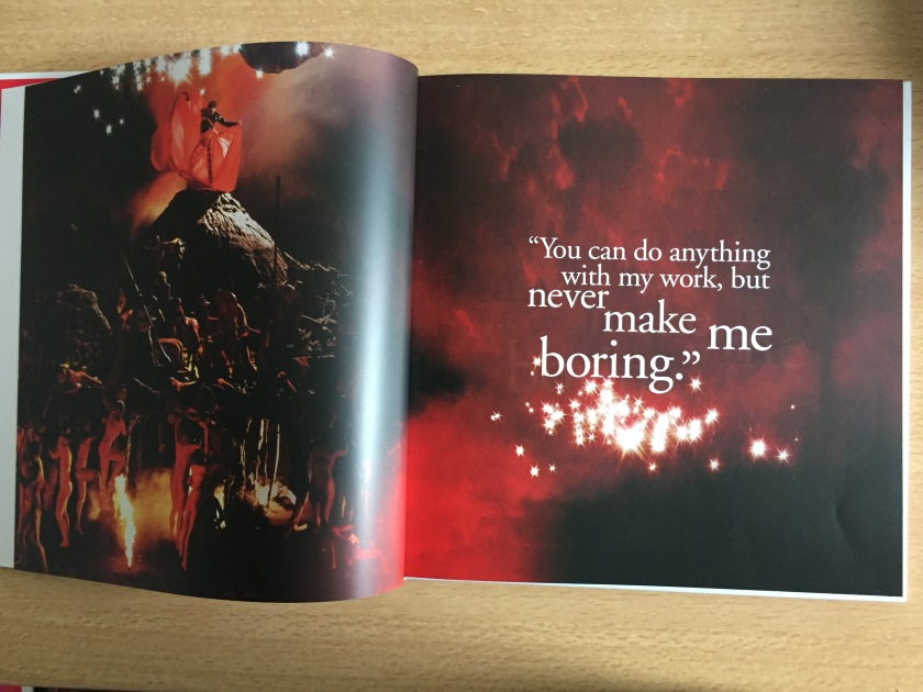 A 2-page spread from the Never Boring book about Freddie Mercury. The left page shows Freddie fanning out a red cape behind him as he stands on a tall model of a mountain or volcano, while people gather around the bottom as if trying to reach him and worship him.