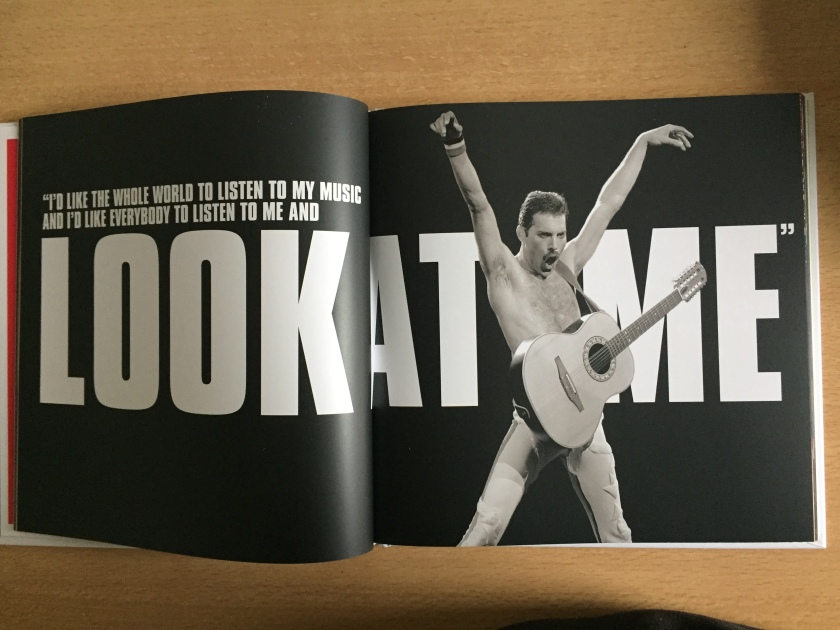 A 2-page spread from the Never Boring book about Freddie Mercury. On the right page, against a black background, a topless Freddie stands triumphant, ams raised up and outwards above his head and his legs spread, giving him a star shape.A guitar hangs around his waist from a strap over his neck, and his mouth is open as if shouting. White text on the left page reads I'd like the whole world to listen to my music, and I'd like everybody to listen to me and look at me.