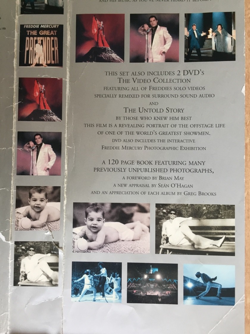 Section of the outer cover sheet of the Freddie Mercury Solo Collection box set. Various photos of Freddie, from a baby through to his 80s concerts and music videos, surround text that describes the contents of the 2 DVDs in the set, featuring his music videos and a documentary.