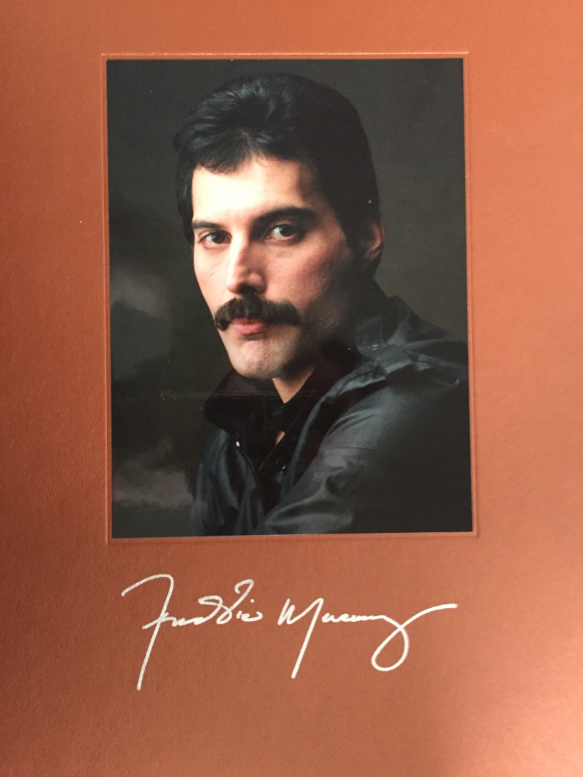 Head and shoulders photo of Freddie Mercury wearing a leather jacket, above his signature in silver writing, from the cover of the book in his Solo Collection box set.