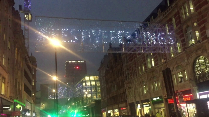 A rectangular strip of lights stretched across Oxford Street, that can be lit up in any combination to form images and messages. Here the lights are displaying the hashtag Festive Feelings.