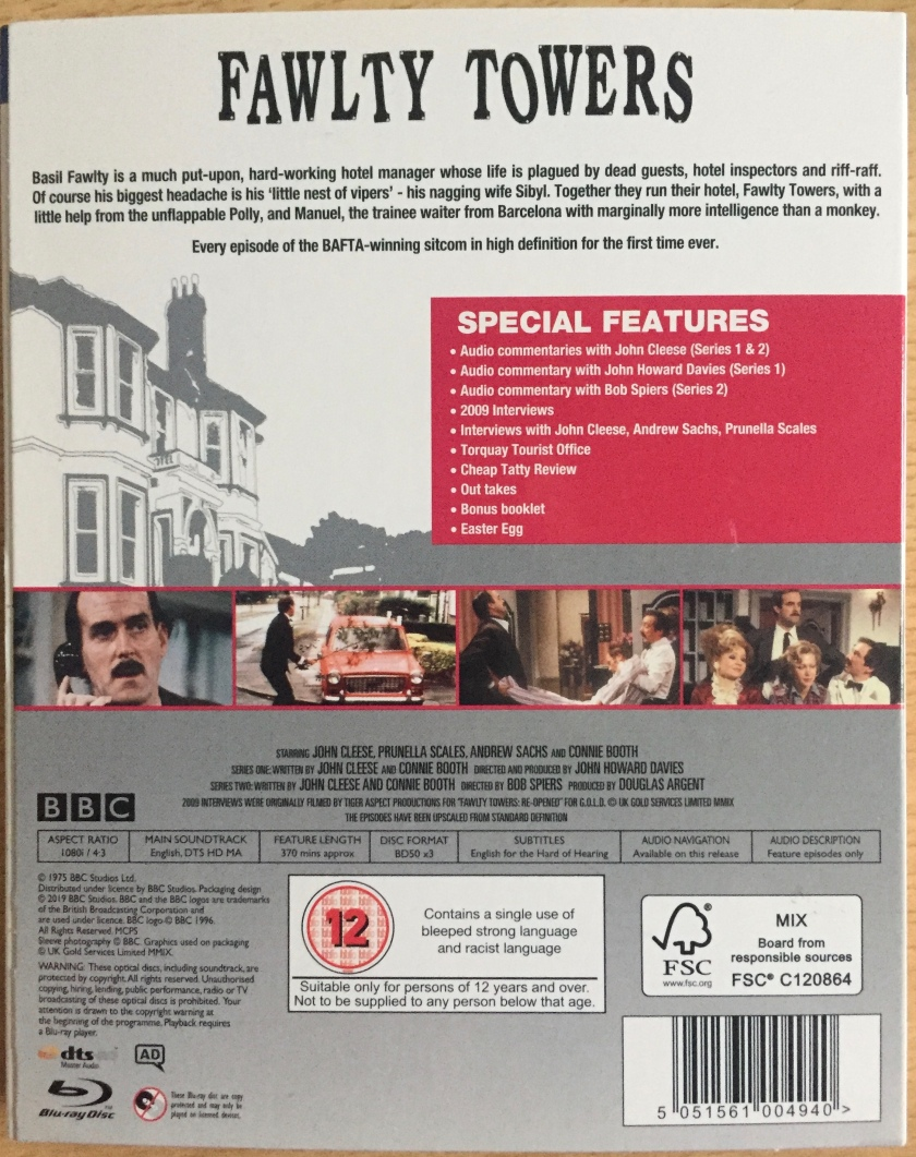 Back cover of the Blu-ray case for Fawlty Towers, with a background image of the hotel, and a small row of photos from the show. The special features listed include audio commentaries by John Cleese and the directors of each series, interviews, outtakes and more. The set also includes English subtitles, audio description and audio navigation.