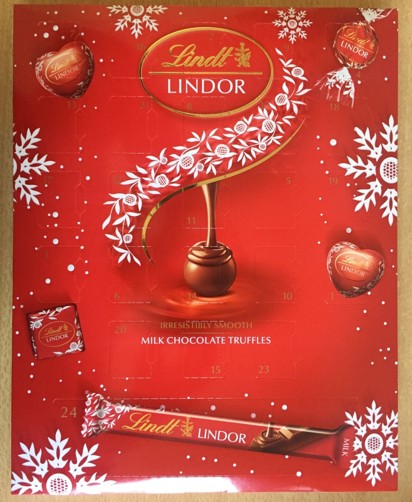 Lindt Milk Chocolate Truffles Advent Calendar. The red box has white leaves and snowflake decorations on it, and a large truffle having chocolate poured over it in the centre. The numbering on the doors is gold on the red background. The bottom door is much longer than the others, as it contains a Lindor chocolate bar rather than a small truffle.