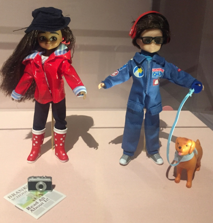 2 dolls, one of which is wearing dark glasses and an all-in-one blue suit, and has a golden coloured dog on a lead. The other doll is wearing a shiny red jacket, black trousers and red boots with white spots.