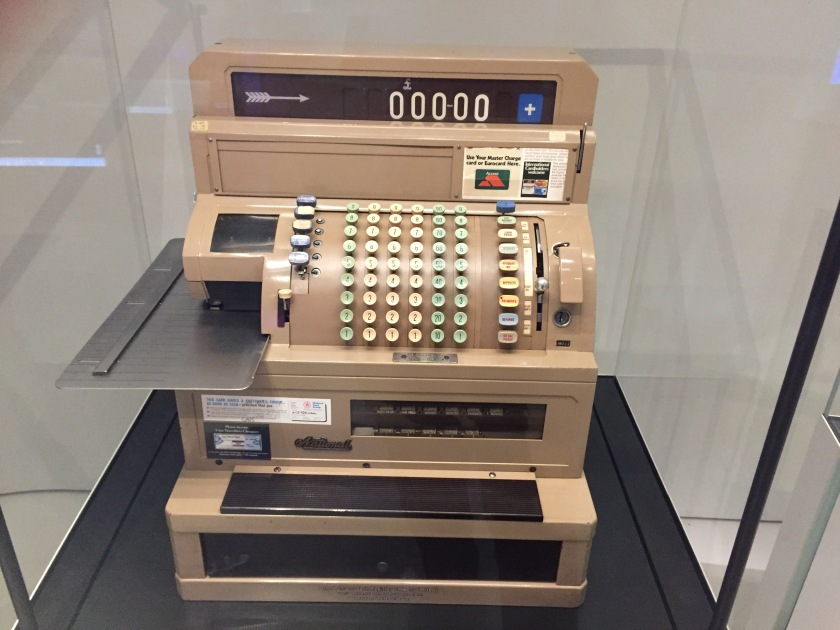 A large cash register till in a glass case at the Science Museum. It has many rows of buttons on the curved central section, a draw at bottom, and a narrow screen at the top with white numbers on a black background.
