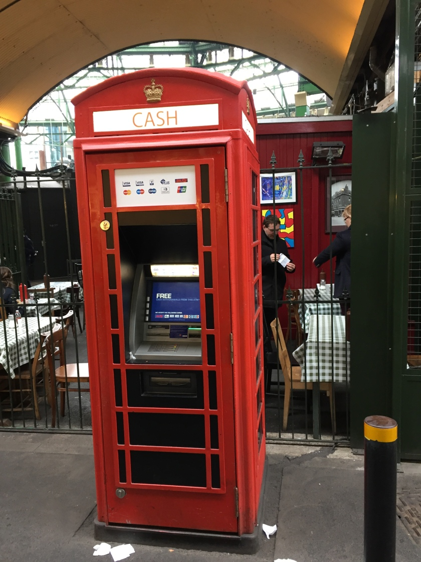 Cash machine embedded in a tall red phonebox.