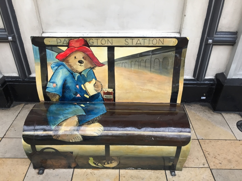 Bench at Paddington station, painted to look like Paddington Bear is sitting on it, in his red hat and blue duffel coat, smiling as he eats a sandwich, with his suitcase and a couple of pigeons on the floor in front of him.