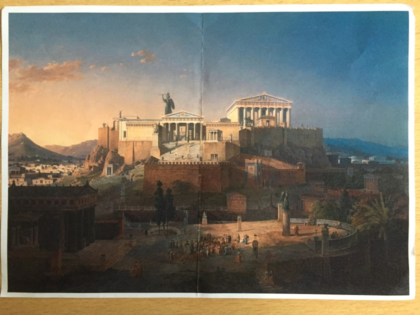 Colour photocopy of a painting by Leo von Klenze, showing the Parthenon and a similar but smaller building next to it. They are built high above a large area of land with a curved edge, in which a group of people are gathered between a building on the left and a statue on the right.