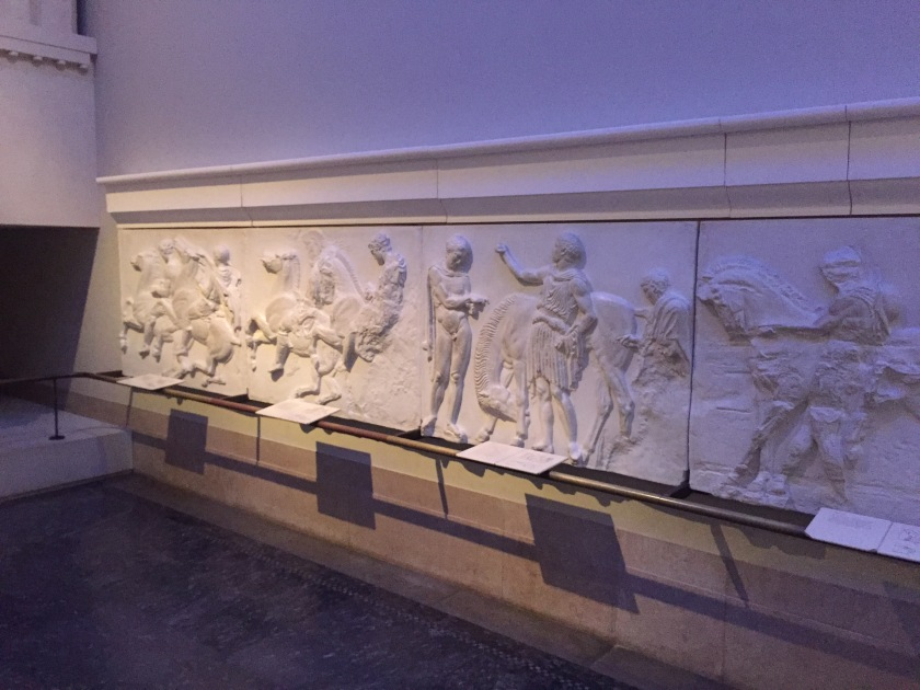Lifesize tactile cast replica of part of the sculptural frieze from the Parthenon, showing a variety of people, some on horseback and some standing.