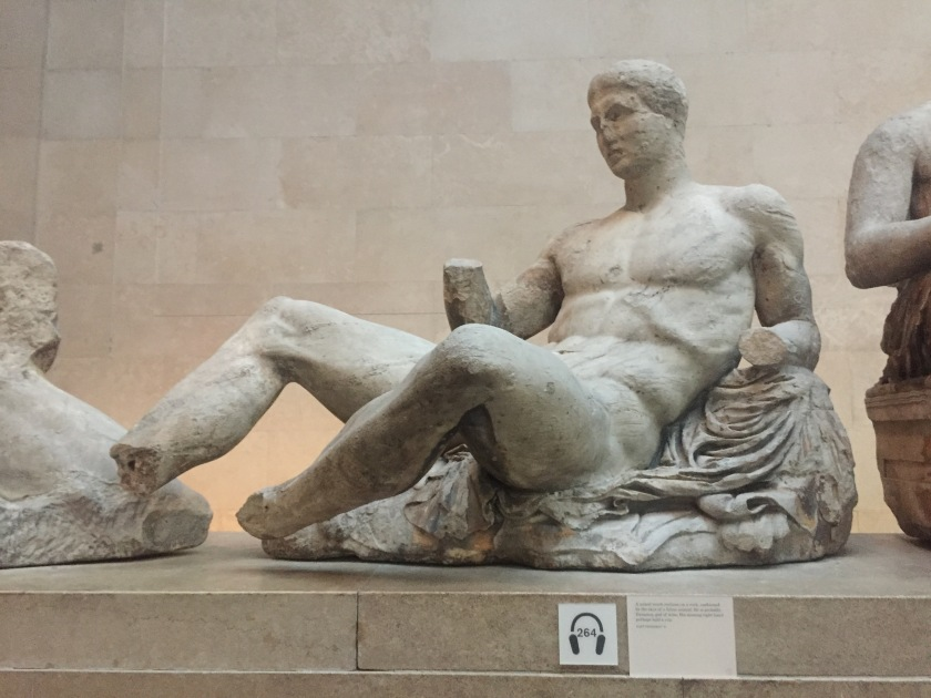 Statue of a naked young man reclining on a rock. The statue shows signs of wear and tear, and his hands and feet are missing.