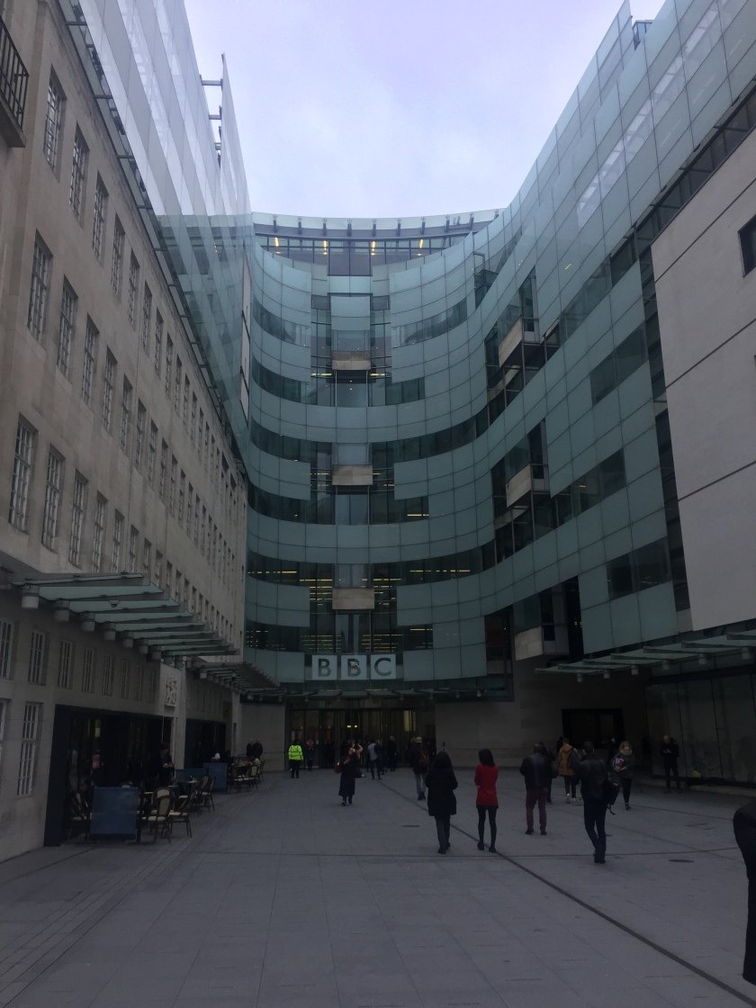 View of BBC Broadcasting House, arching all the way around the path to the entrance ahead. The BBC logo, each letter in a white square, is over the doors. The bottom half of the left wall is from the old stone building, with row of windows for each floor. The rest of the building is a tall, modern glass structure, with a mixed pattern of opaque and clear windows.