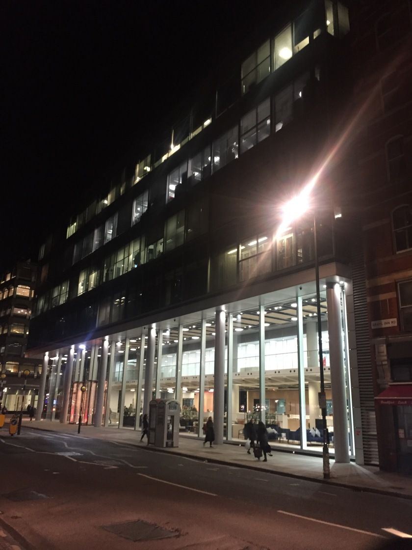 The exterior of the very wide and tall ITN Productions building. Tall glass windows span the entire width of the brightly lit ground floor, with 2 revolving doors in the centre, while there are smaller office windows in the floors above.