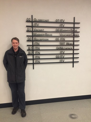 Glen smiling as he stands next to a tall sign, made of black bordered rows with black lettering, showing what's on each floor of the building. Most say ITN or ITV, but the sign also mentions Globecast, Warner Brothers, TRT World and Metspack, plus the reception desk.