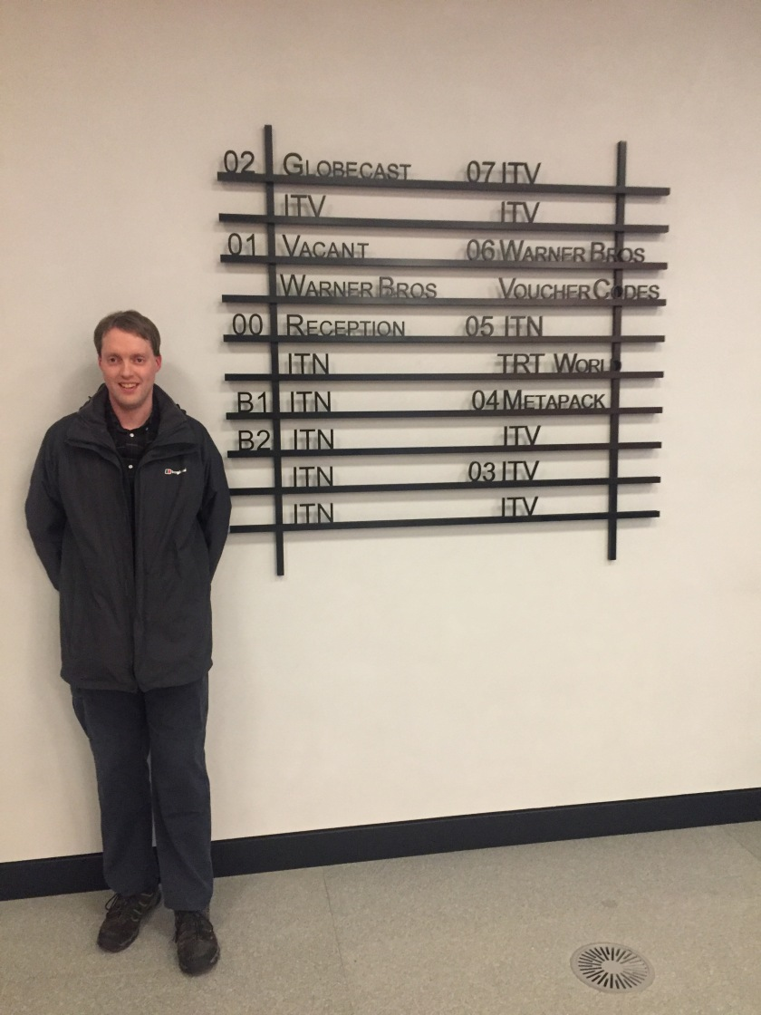 Glen smiling as he stands next to a tall sign, made of black bordered rows with black lettering, showing what's on each floor of the building. Most say ITN or ITV, but the sign also mentions Globecast, Warner Brothers, TRT World and Metapack, plus the reception desk.
