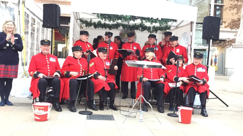 A choir of Chelsea Pensioners, a mixture of men and women who are smiling while wearing red jackets with large round buttons and many medals, along with black trousers. Their female conductor, smiling and applauding them to one side, is wearing a Christmas jumper, a tartan skirt and black tights.