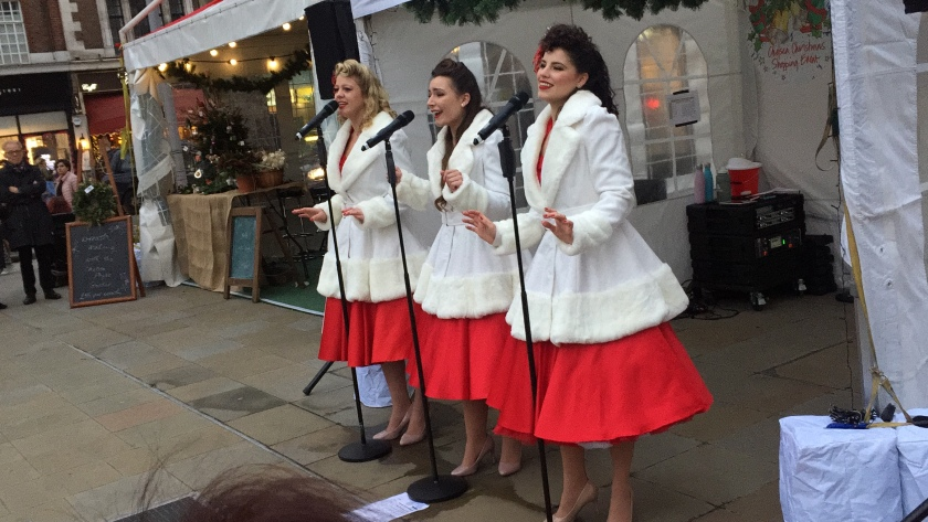 The Satin Dollz, 3 ladies smiling as they stand and sing at microphones, gesturing with their arms as they perform. Each of them is wearing a long white jacket with thick fluffy collars, cuffs and hem, over a large red skirt that swirls around them when they turn.
