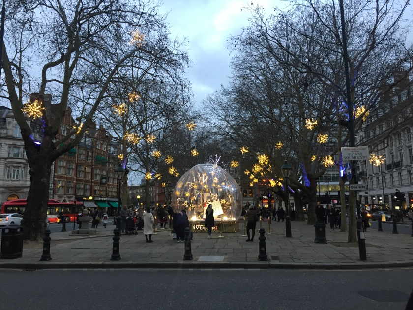 Sloane Square, with large lit-up star decorations hanging from trees along its length. At the end of the square nearest us is a large snow globe structure by a company called Bvlgar, in which people can sit on a director's chair to have their photos taken.
