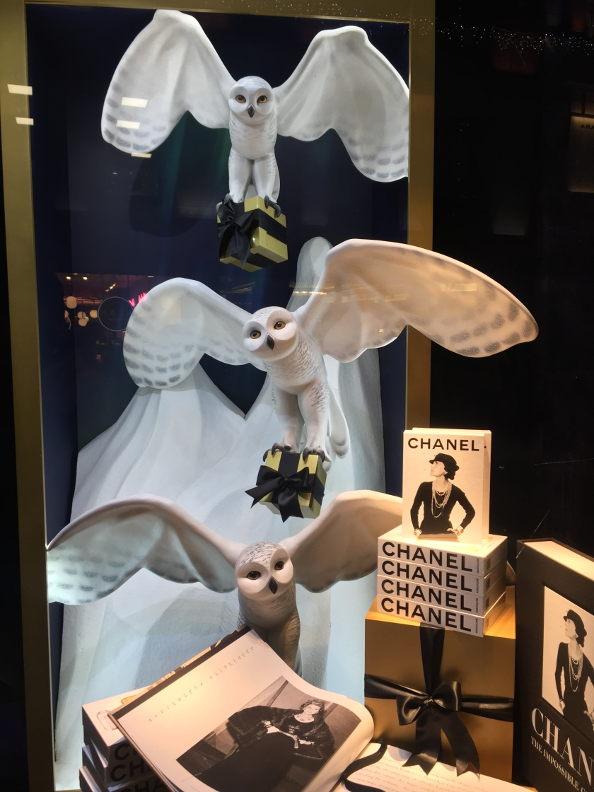 Models of 3 large white owls in flight, one above the other, in a Harrods window display. Each is carrying a small gift wrapped box with its talons. Beneath them is a pile of books about Chanel, with a lady posing with her hands on her hips on the cover.