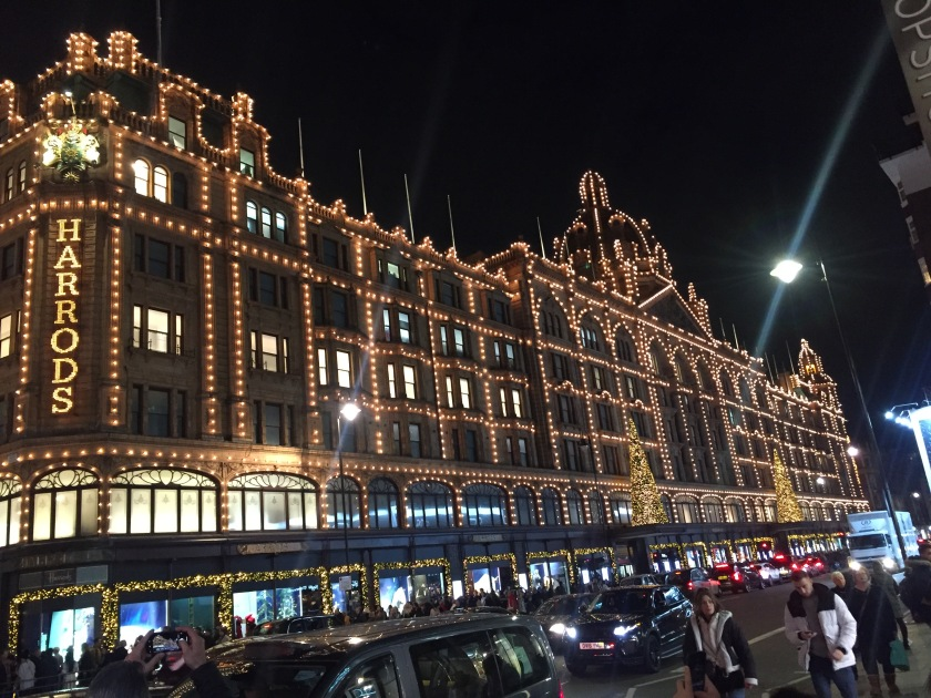 The huge and ornate Harrods building covered in bright lights, including the word Harrods in big letters down the corner wall.