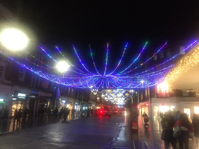 A huge chandelier-like structure, made of many lines of lights curving out and upwards from a central ring of light, spans the entire width of Exeter High Street. Other decorative Christmas lights can be seen across the street in the distance.