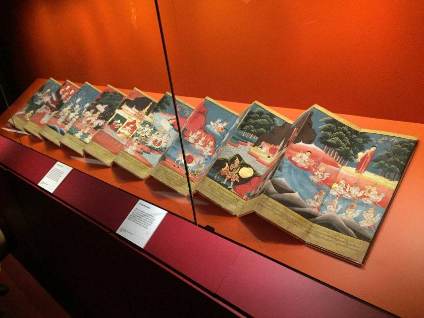 A long concertina book, opened up to reveal the detailed colourful artwork inside, illustrating Buddha's journey through life.