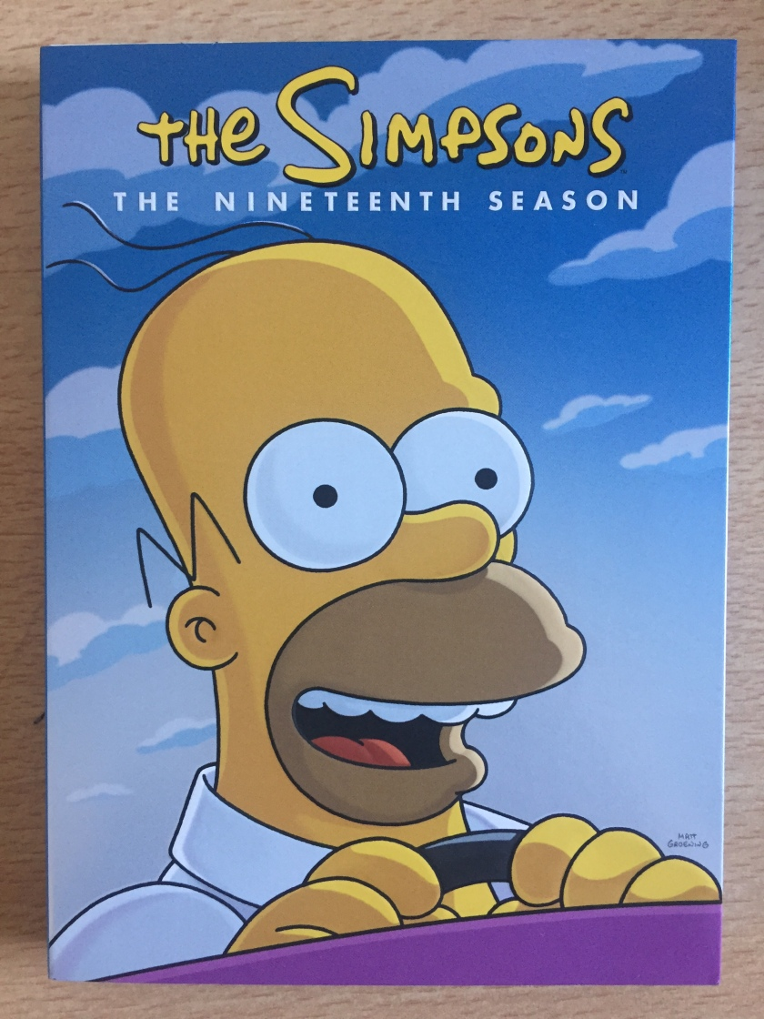 Front cover of the DVD box set for The Simpsons Season 19, showing Homer smiling as he drives his car.