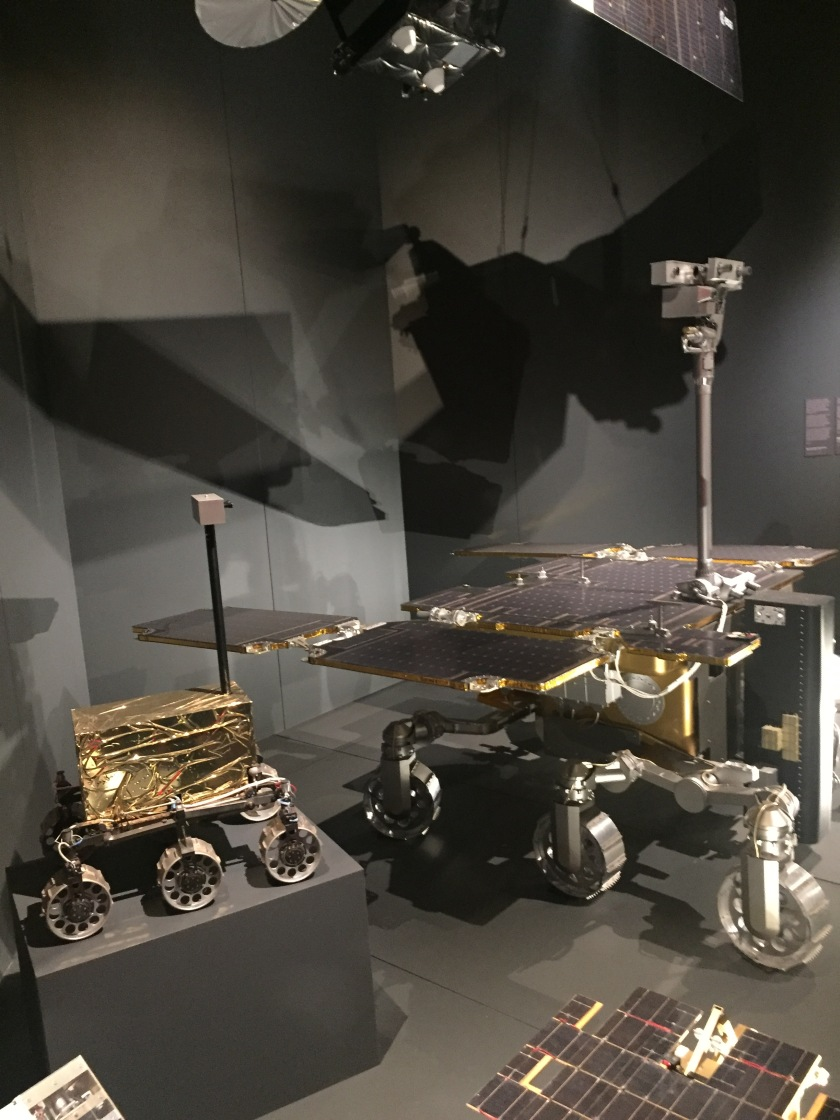 Robotic research vehicles for studying the surface of mars. One is very small, with the body consisting of a shining gold box, while the other is much larger and covered in solar panels. Both vehicles have 3 wheels on each side, and a long pole sticking up with cameras and sensors on the top.