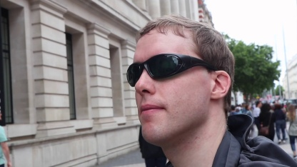 Close-up of Glen wearing his green-tinted sunglasses while standing outside the Science Museum.