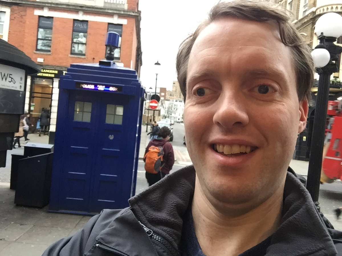 Selfie of Glen smiling, in front of a big blue police phone box that looks like Doctor Who's Tardis.