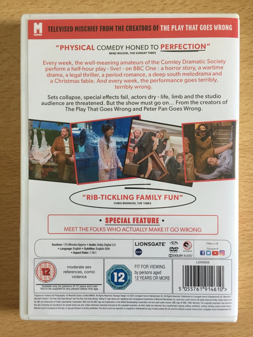 Back cover of the DVD for Series 1 of The Goes Wrong Show, showing a few photos from the show. Review quotes state that it's Physical comedy hone to perfection, and it's Rib-tickling holiday fun. The DVD is rated 12.