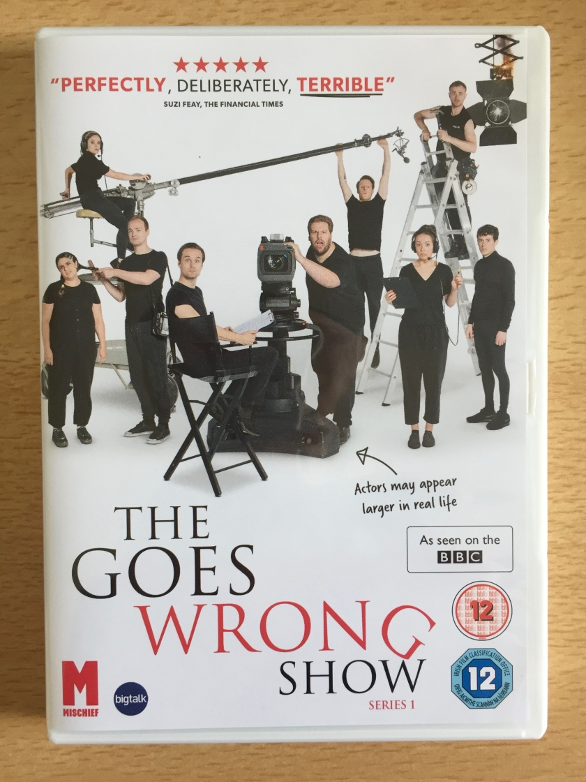 DVD cover for The Goes Wrong Show, series 1, showing the cast posing with filming equipment, including a camera, an overhead boom microphone and lighting.