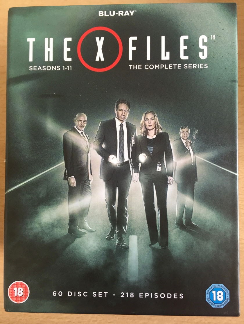 Cover for the Blu-ray set of The X Files, with all 11 seasons, 218 episodes, on 60 discs. The image shows Mulder, Scully, Skinner and the Cigarette Smoking Man in front of a bright light.