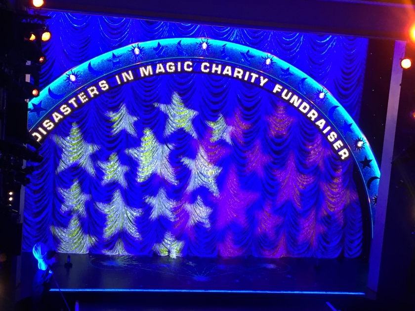 In front of a blue stage curtain, with bright stars projected on to it, is a tall arch spanning the width of the stage, featuring lit-up words that say Disasters In Magic Charity Fundraiser.