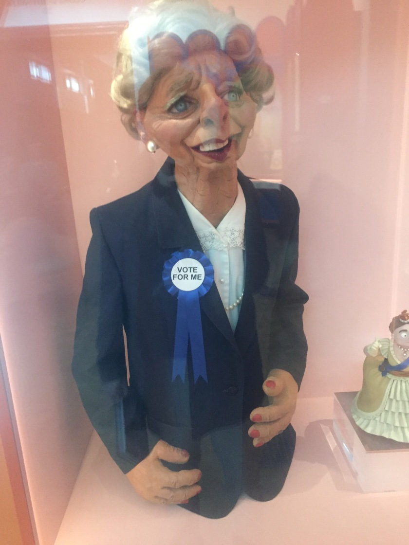 Large puppet of Margaret Thatcher, from the Spitting Image TV series. Consisting of just her head and upper body, she has slightly exaggerated facial features, while wearing a navy jacket over a white blouse, and a round ribbon attached to her jacket that says Vote For Me.