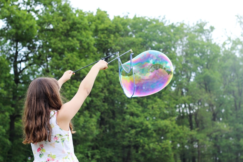 A young girl outdoors using a giant bubble wand, producing a large bubble that has a rainbow-coloured effect as it reflects the light.
