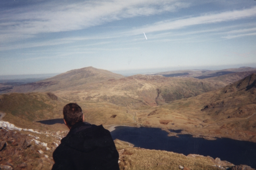 Standing on a hill high above a lake, a man looks out over the beautiful mountainous scenery of Snowdonia, under a blue sky with wispy clouds.