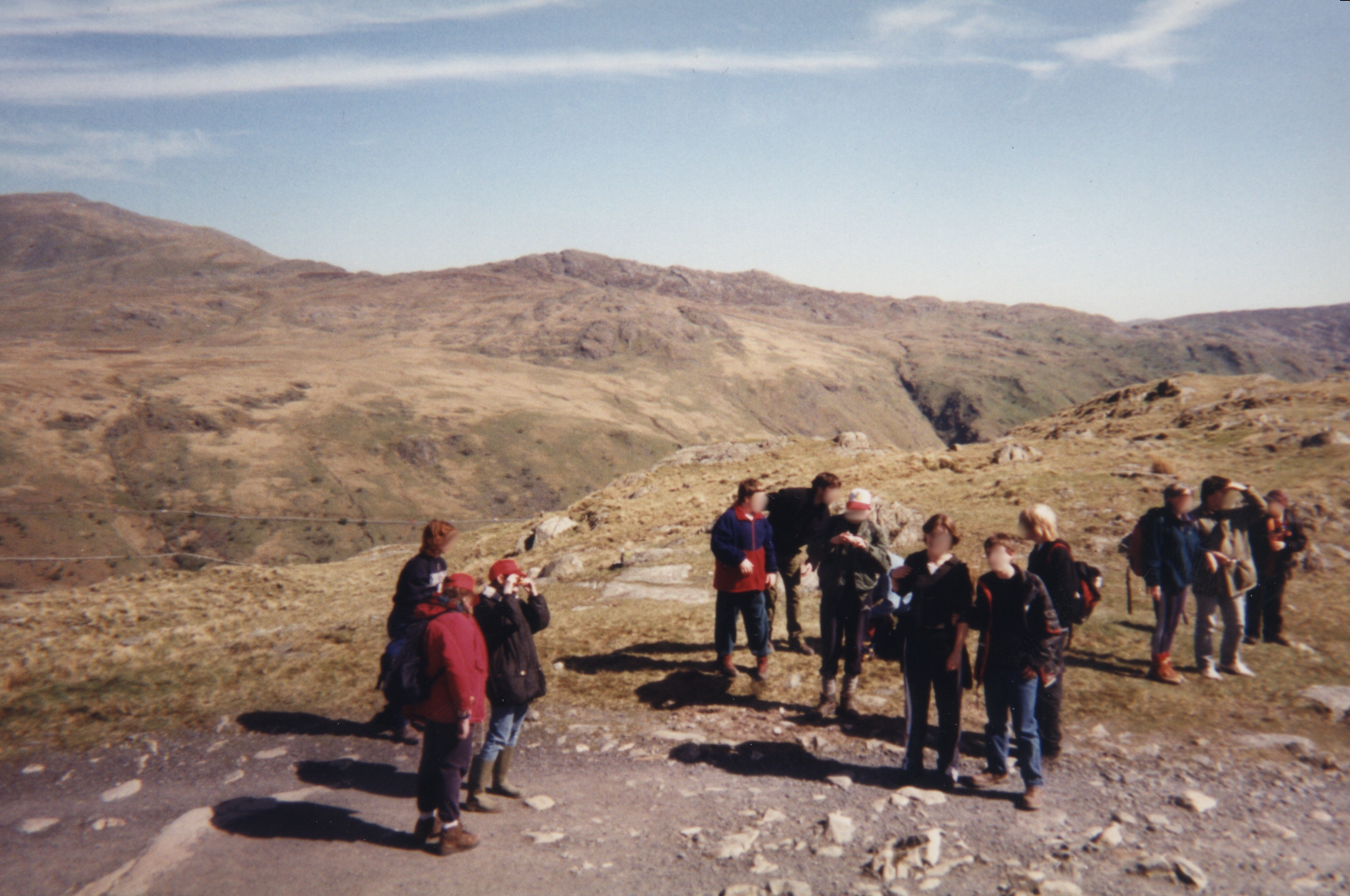 Group photo of teenagers and school staff, their faces blurred out for privacy, admiring the mountainous scenery surrounding them in Snowdonia.
