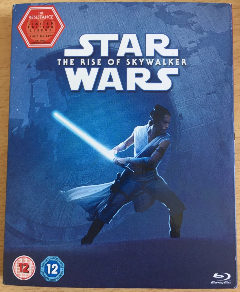 Blu-ray front cover for Star Wars - The Rise Of Skywalker, showing Rey against a blue background, in an attack pose as she prepares to swing her lightsaber.