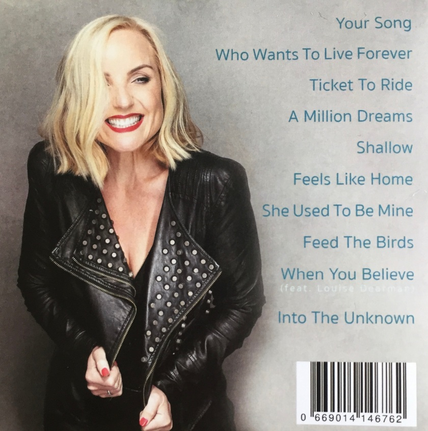 Back cover of the Kerry Ellis album feels like home. To the left of the list of tracks, Kerry is is grinning widely as she partially holds open her black leather jacket, revealing lots of metal studs lining the inside.