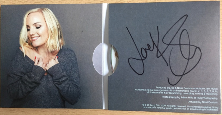 The unfolded sleeve for the Kerry Ellis album Feels Like Home. On the left side is the blonde singer smiling with her eye closed and her hands holding the top of her grey jumper. On a grey background on the right side is Kerry's signature in black, filling three quarters of the space, above small credits in white text in the bottom right corner.