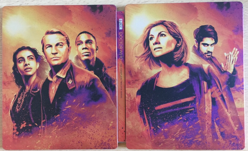 Steelbook cover for the blu-ray set of Doctor Who Series 12, spread open so that the artistic portraits of the cast members on the back and front covers are both visible. On the right, the front cover shows the Doctor and the Master, while the back cover on the left shows companions Yasmin, Graham and Ryan.