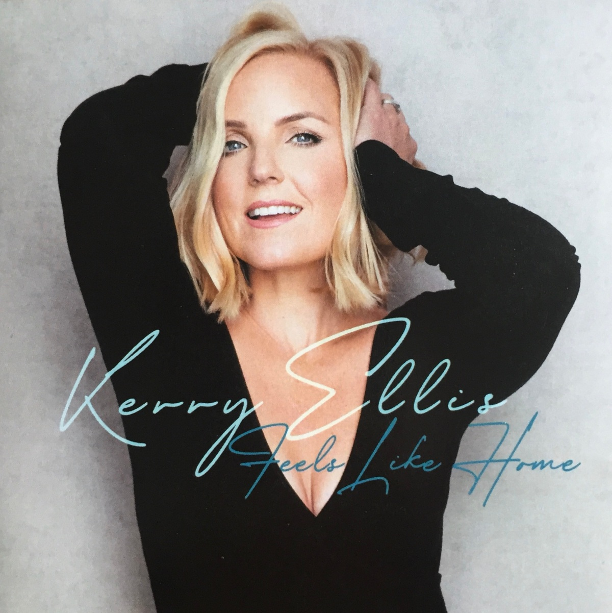 Cover for the Kerry Ellis album Feels Like Home, showing the singer wearing a black top with a deep v-neck, and running her hands back through her blonde hair as she smiles.