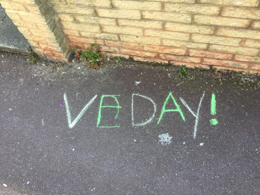 The text V E Day, followed by an exclamation mark, written on the pavement in large coloured chalk letters.