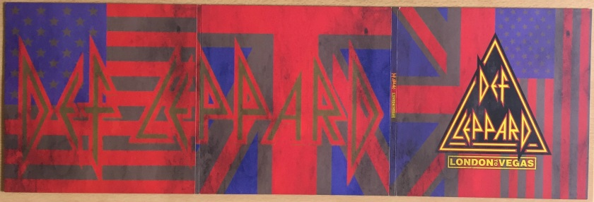 Outer side of the large 3 panel foldout sleeve from the Def Leppard London To Vegas box set. It features faded versions of the Union Jack and American flags across the background, the white areas having become grey while the reds and blues are still visible. A bit of dirt has been added to the flags as well. Across the left 2 panels, the Def Leppard logo spreads all the way across in large faded letters that are difficult to see. The far right panel, which forms the front of the sleeve when folded, as the Def Leppard logo in its more traditional clear form, inside the yellow and red edged triangle, with London To Vegas written beneath.